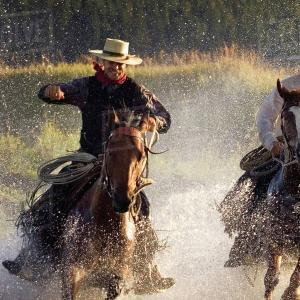 Cowboys gallop across the Rio Grande River
